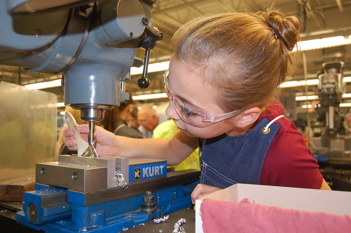 A photo of a female student using machinery.